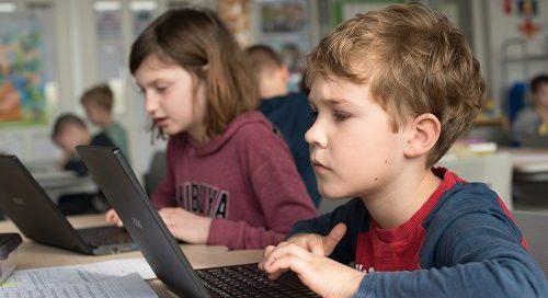 kind werkt op laptop geconcentreerd